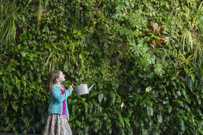 A young girl standing in front of a wall covered with ferns and climbing plants.