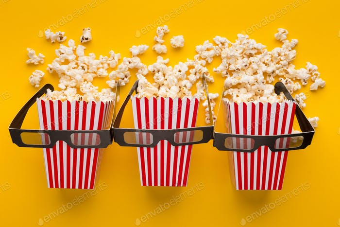 Buckets of popcorn on yellow background, top view