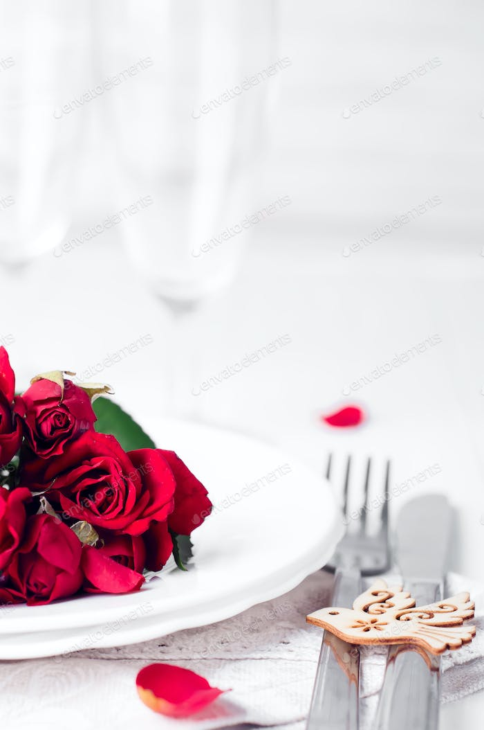 Festive table setting with beige roses, wine glasses, napkins and cutlery,