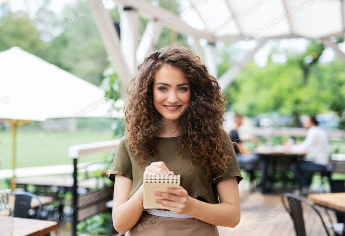 Portrait of waitress standing on terrace restaurant, holding order pad