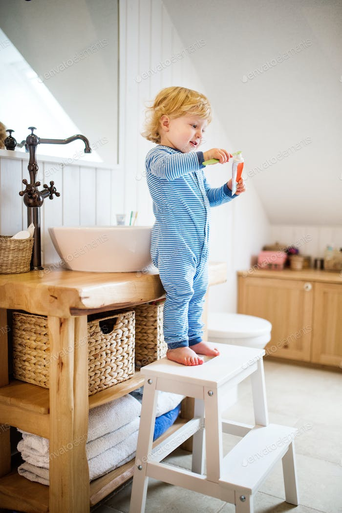 Cute toddler boy brushing his teeth in the bathroom.