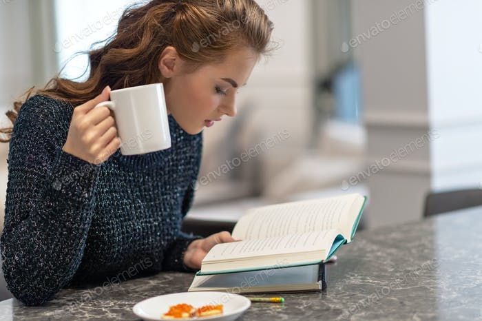 Attractive woman sitting on the kitchen  reading a book.