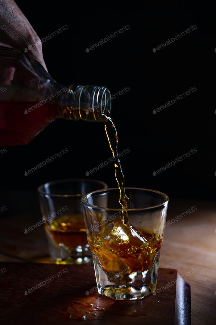 Gießen Sie den Alkohol in das Glas