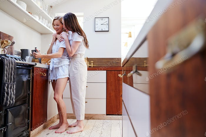 Female Gay Couple At Home In Kitchen Making Fresh Coffee