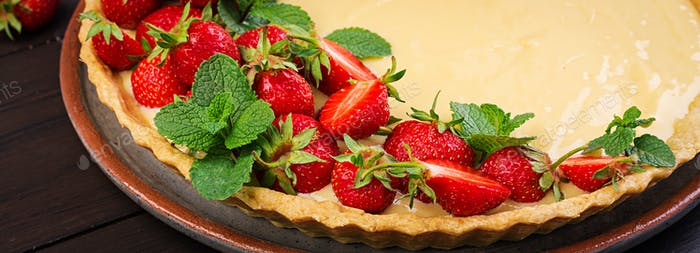 Tart with strawberries and whipped cream decorated with mint leaves on dark background. Banner