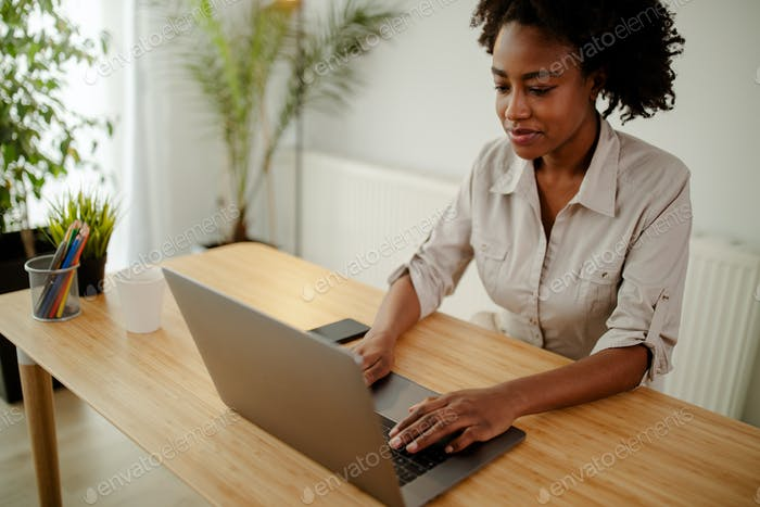 Concentrated afro american copywriter updating software on laptop computer in office.