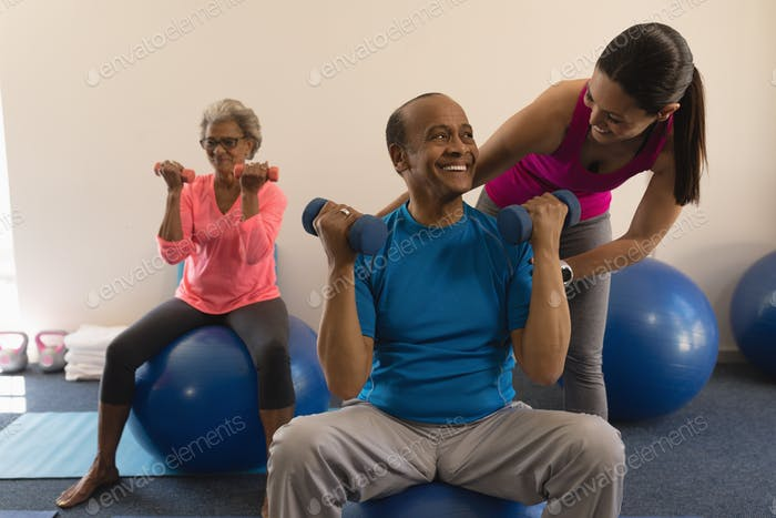 Front view of happy female trainer assisting senior man in fitness studio