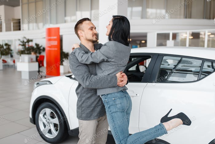Couple buying new car, man and woman hugging