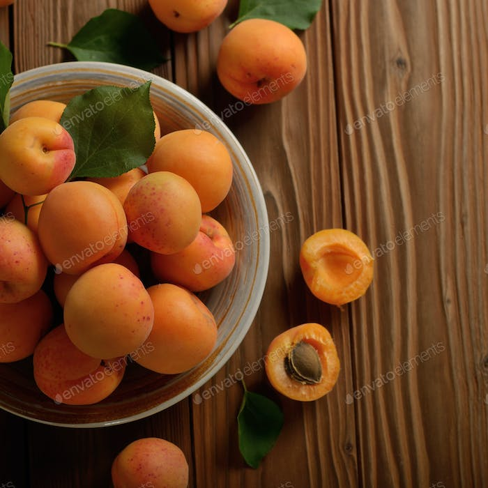 Top view of Clay dish full of ripe apricots on wooden table
