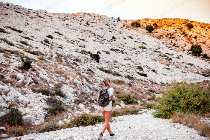 Hiker woman with backpack on trekking trail, travel and active lifestyle concept