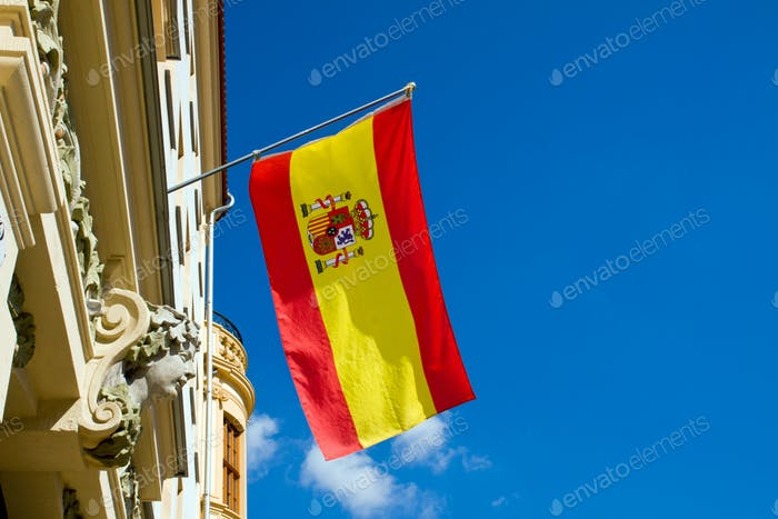 Spanish flag flying at an old building