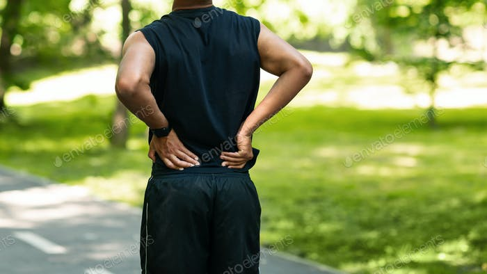 Black guy having back pain during his morning run at park, copy space