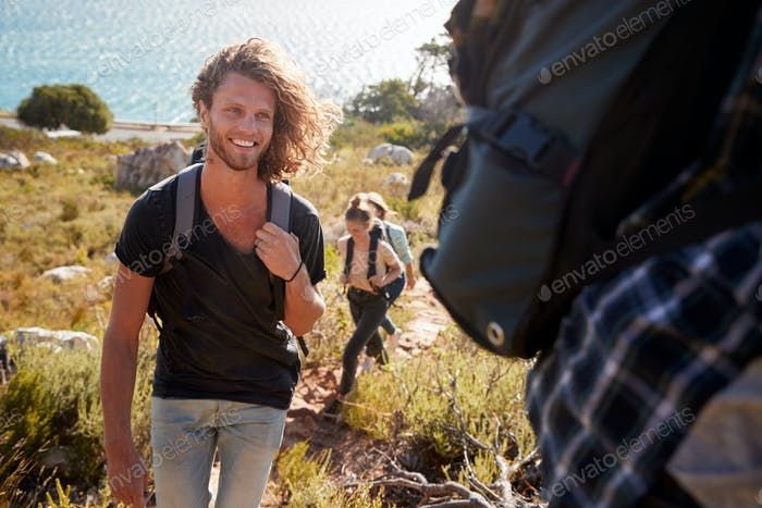 Young adult white man hiking with friends in countryside by the coast, smiling to camera