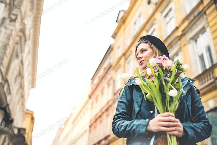 Junge Frau mit Blumen in sonniger Frühlingsstadt.
