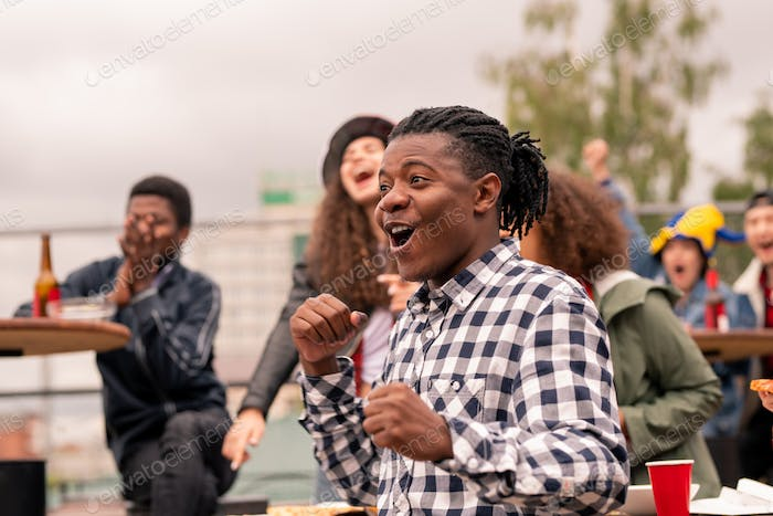Young male football fan and his friends expressing excitement during match