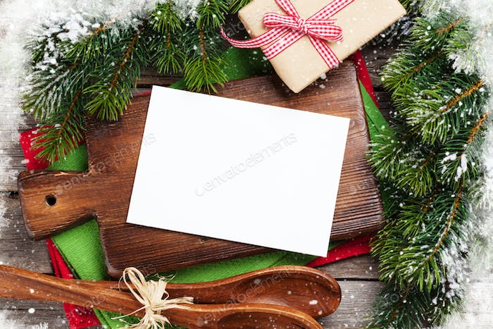 Christmas greeting card over cooking table and utensils
