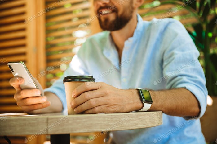 Bearded man in cafe outdoors using mobile phone