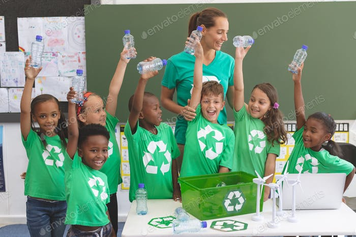 Teacher and student standing together with plastic bottles in their hands in classroom
