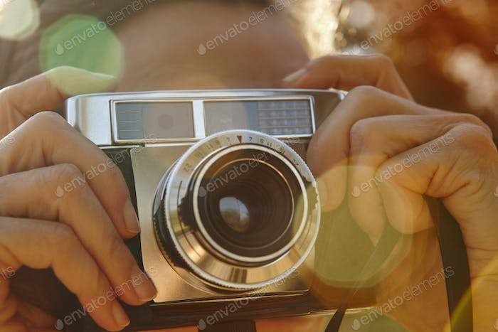 Woman taking pictures with vintage camera. Travel background. Fall season