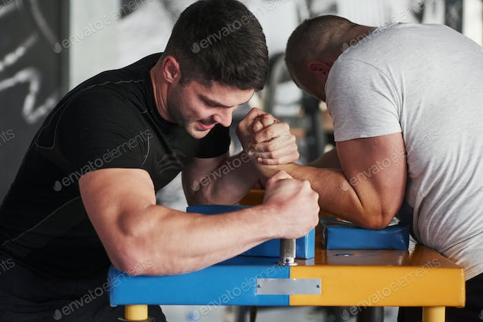 People is struggling to win. Arm wrestling challenge between two men. Match on a special table