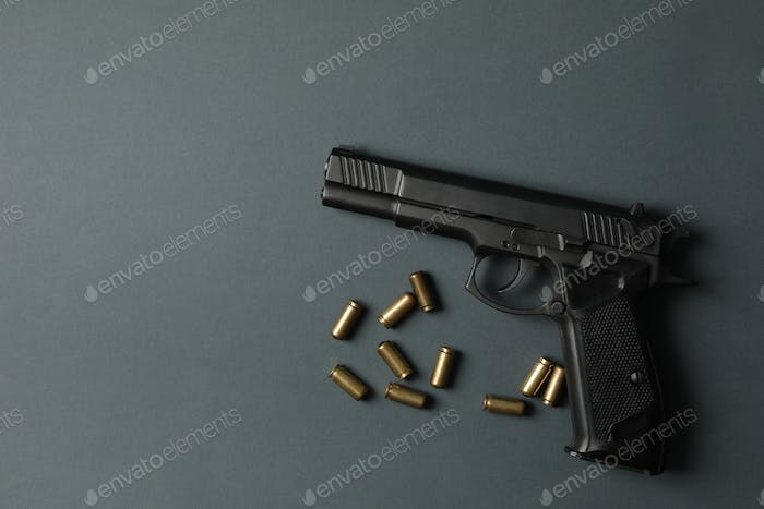 Pistol and traumatic bullets on dark gray background. Self defense weapon