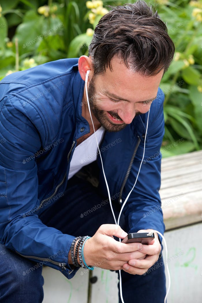 Smiling guy listening to music on mobile phone
