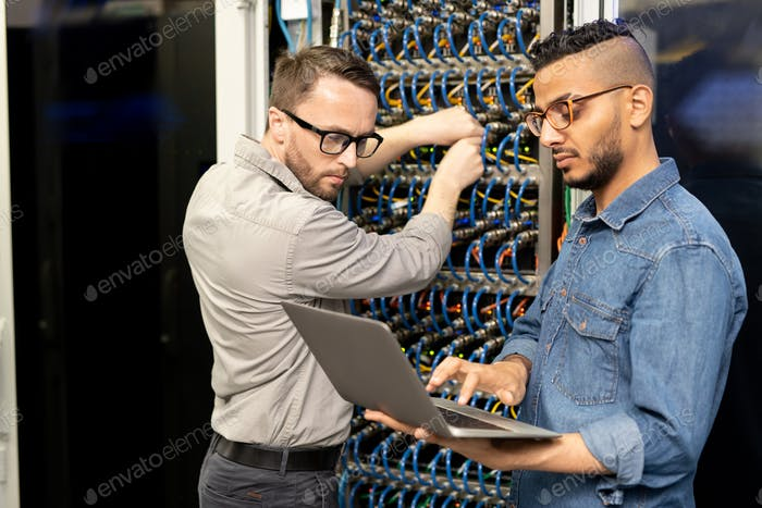 Multi-ethnic IT engineers setting up computer cluster