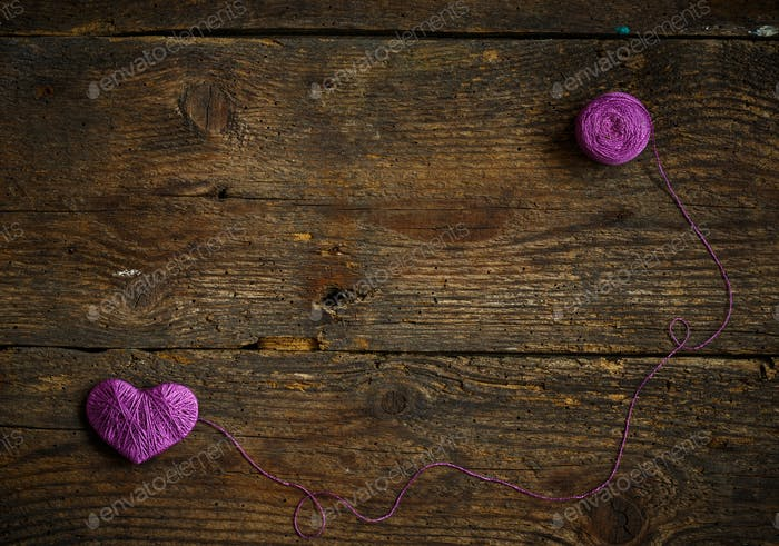 Purple Heart with a ball of thread on on old shabby wooden backg