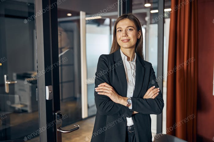 Pleased businesswoman in business attire looking ahead