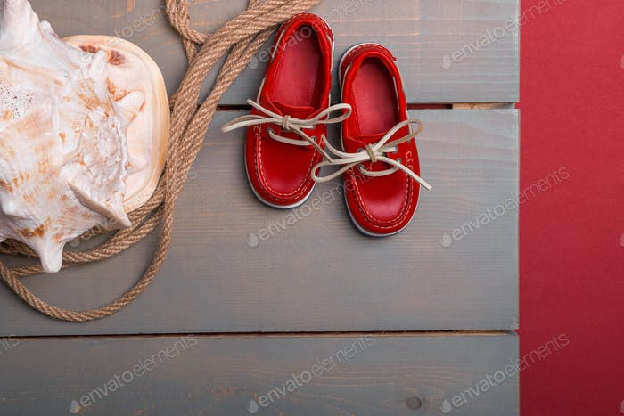 Red boat shoes near big shell and rope on wooden background. Top view . Copy space. Frame.