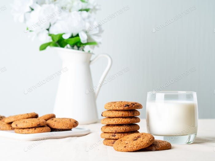 Chocolate oatmeal cookies and milk in glass, healthy snack. Light background, grey light wall