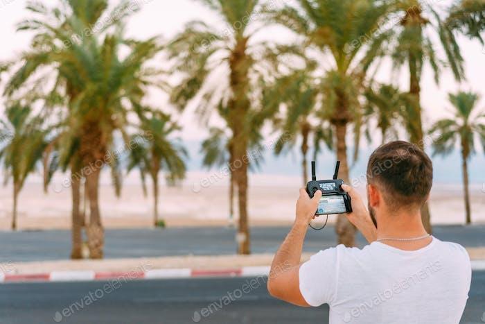 Guy steuert Drohne mit Fernbedienung