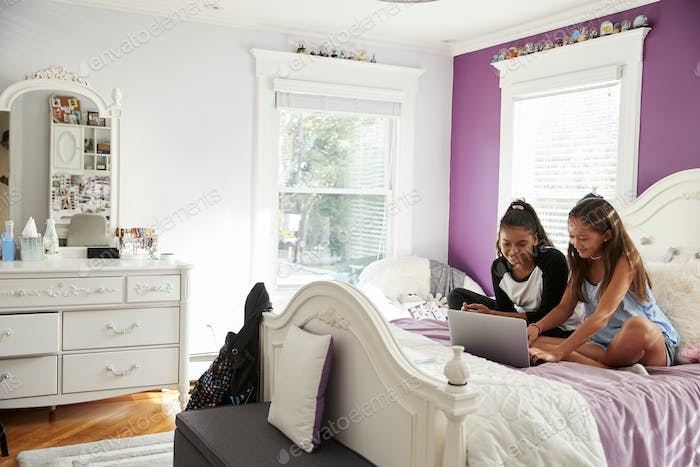 Two girlfriends in bedroom sitting on bed using a laptop