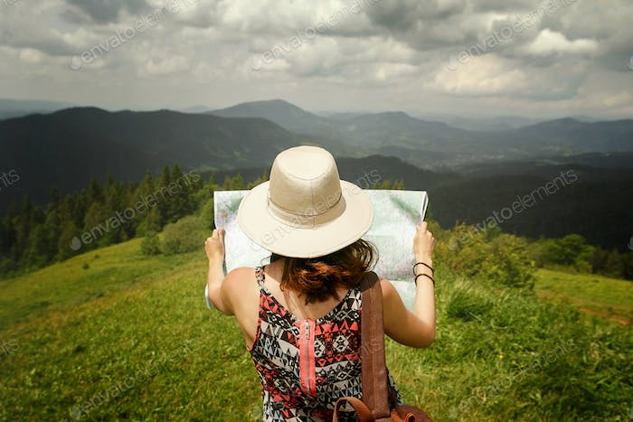 Woman traveler with backpack holding map and exploring on top of mountains