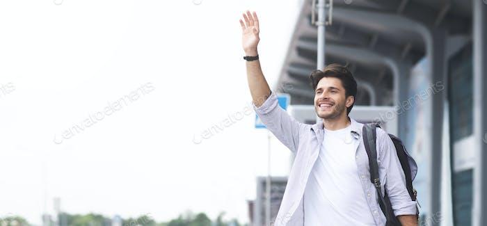 Young man waving hand near airport building, panorama