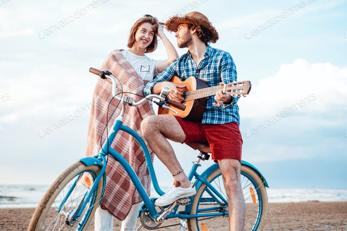 Two attractive people are standing with their bicycle and a guitar. Both of them are smiling