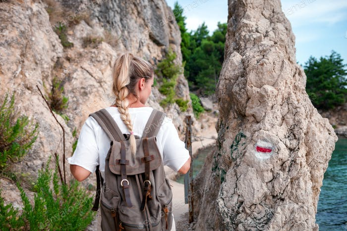 Tourist woman with backpack looking at path sign, discovering while traveling