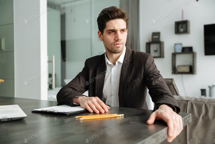 Serious young businessman working indoors