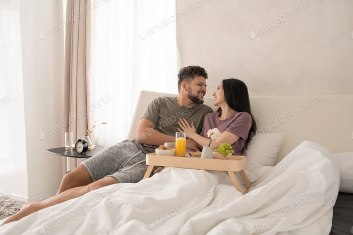 Happy young couple enjoying breakfast in bed