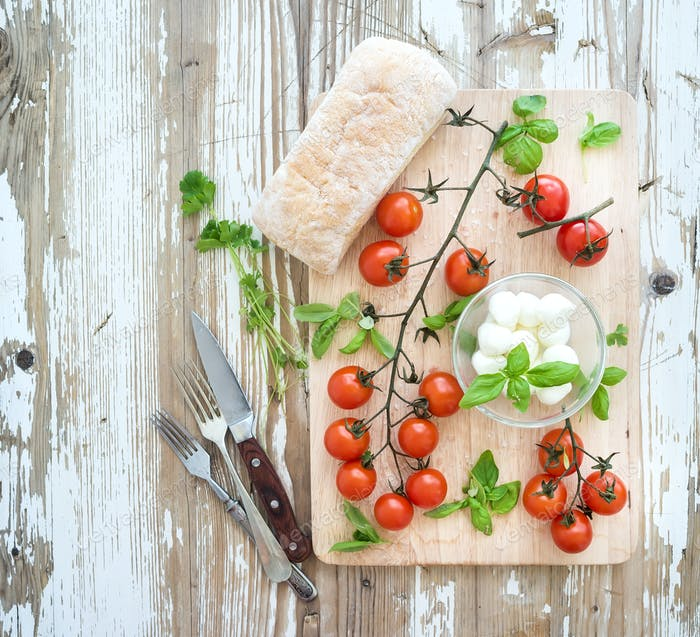 Ciabatta bread with banch of cherry-tomatoes, basil and mozzarella cheese on rustic wooden board