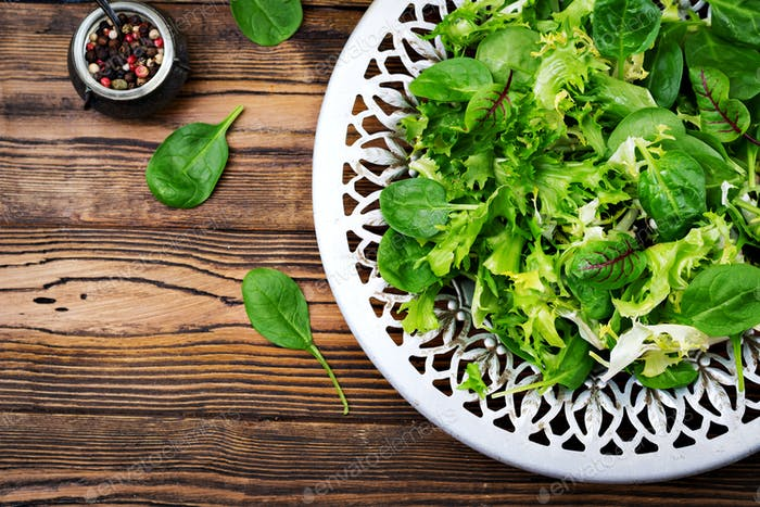 Fresh leaves of mix salad in a bowl on a wooden background. Flat lay. Top view