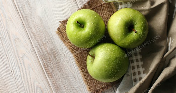 Wet green apples on canvas