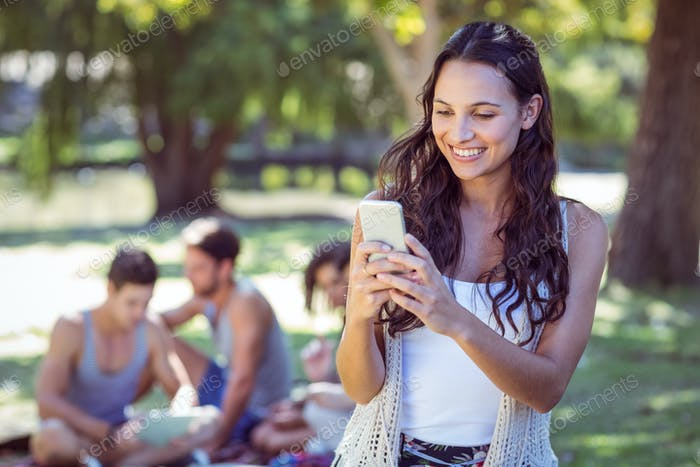 Pretty hipster using her smartphone on a sunny day