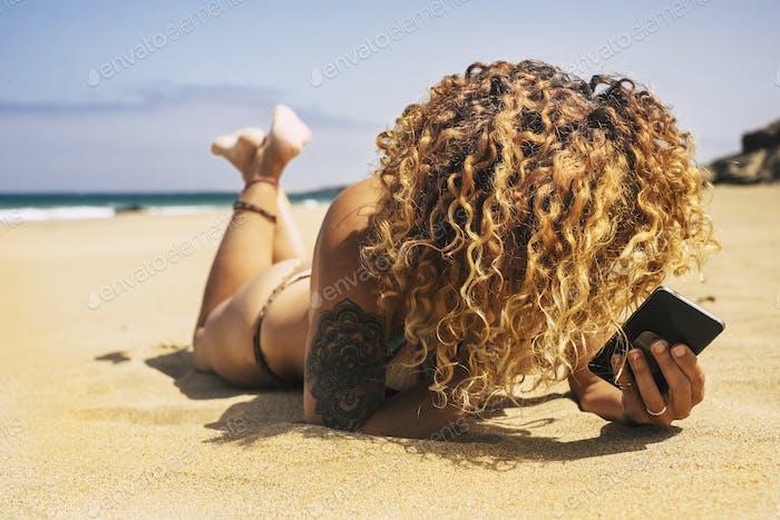 Beautiful blonde curly long hair woman at the summer beach
