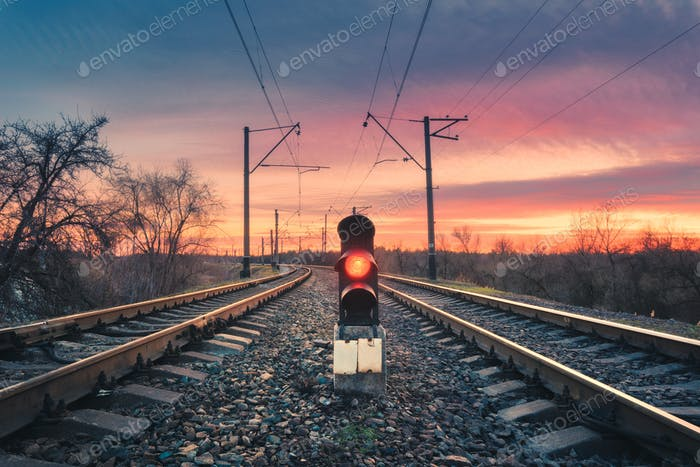 Railway station with traffic light at sunset