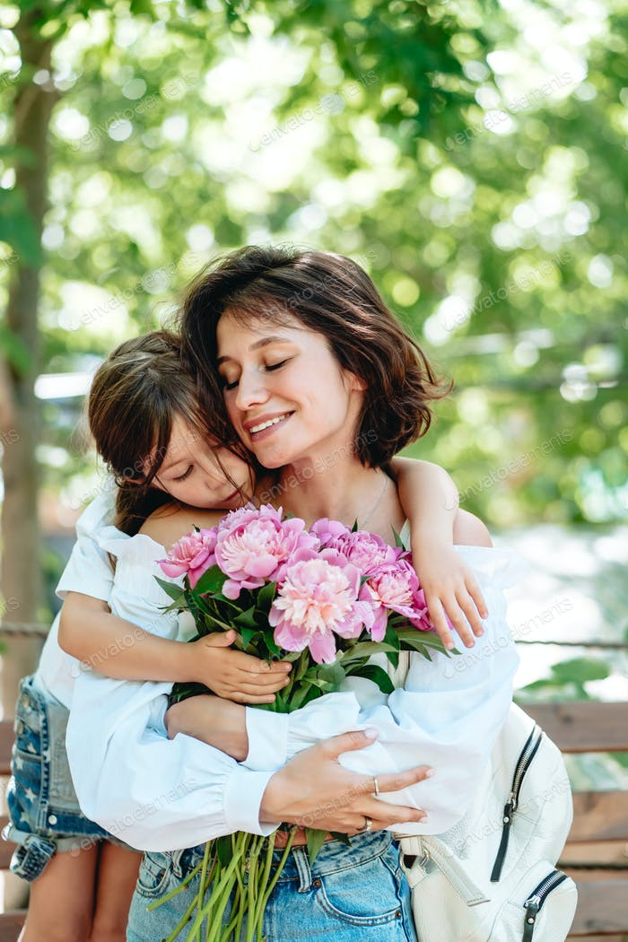 Young mother with a bouquet of flowers is having fun with her daughter