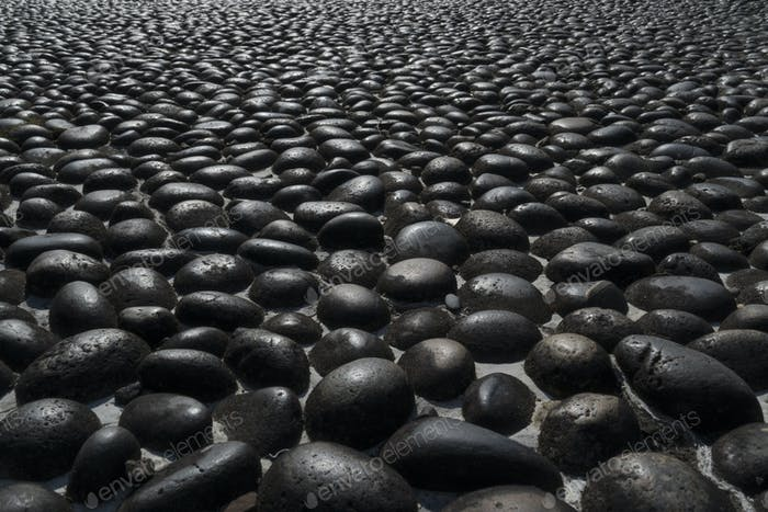 Pavement with round black boulders
