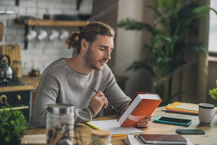 Young handsome man reading Chinese grammar book