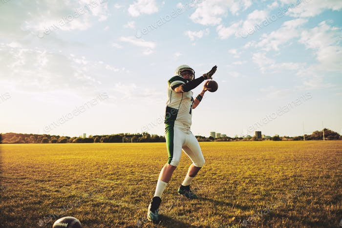 Football quarterback throwing a pass during team practice