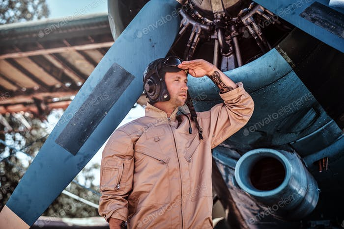 Young pilot is standing near his jet.